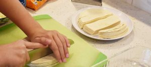 Slicing tortillas for Smoked Green Chile Enchiladas